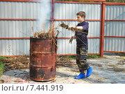 Подросток сжигает мусор на дачном участке. Стоковое фото, фотограф Инесса Гаварс / Фотобанк Лори