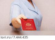 Купить «Женщина протягивает заграничный паспорт Российской Федерации (фокус на паспорте)», фото № 7444435, снято 17 мая 2015 г. (c) Анна Менщикова / Фотобанк Лори