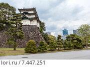 Трехэтажная башня Fujimi-yagura в японском стиле на каменной стене на внутренней территории Императорского дворца на фоне небоскребов в Токио. Япония (2013 год). Стоковое фото, фотограф Кекяляйнен Андрей / Фотобанк Лори