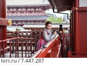 Купить «Туристка с фотоаппаратом стоит в буддистском храме среди красных деревянных конструкций. Asakusa, Senso-ji, Токио, Япония», фото № 7447287, снято 10 апреля 2013 г. (c) Кекяляйнен Андрей / Фотобанк Лори
