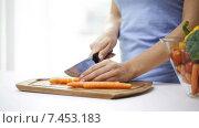 Купить «close up of young woman chopping carrot at home», видеоролик № 7453183, снято 1 мая 2015 г. (c) Syda Productions / Фотобанк Лори