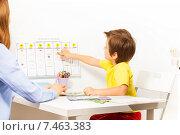Купить «Мальчик изучает дни недели. Ребенок и преподаватель сидят перед пособием на стене», фото № 7463383, снято 15 марта 2015 г. (c) Сергей Новиков / Фотобанк Лори