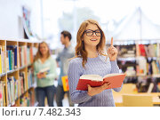 happy student girl or woman with book in library, фото № 7482343, снято 6 марта 2015 г. (c) Syda Productions / Фотобанк Лори