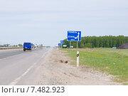 Синий дорожный знак на дороге с надписью Тюмень и автомобиль (2015 год). Редакционное фото, фотограф Екатерина Воронкова / Фотобанк Лори