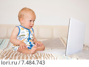 Ребенок с компьютером сидит на кровати (2015 год). Редакционное фото, фотограф Maria Siurtukova / Фотобанк Лори