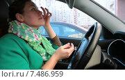 Купить «Молодая женщина прихорашивается, сидя в машине, подготавливается к поездке», видеоролик № 7486959, снято 24 марта 2015 г. (c) Кекяляйнен Андрей / Фотобанк Лори