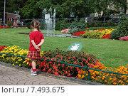 Девочка стоит около газона с цветами (2008 год). Редакционное фото, фотограф Ирина Семчук / Фотобанк Лори