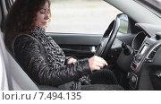 Купить «Молодая женщина пристегивается ремнем безопасности в автомобиле на водительском кресле», видеоролик № 7494135, снято 5 мая 2015 г. (c) Кекяляйнен Андрей / Фотобанк Лори