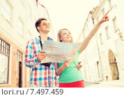 Купить «smiling couple with map and photo camera in city», фото № 7497459, снято 7 июля 2014 г. (c) Syda Productions / Фотобанк Лори