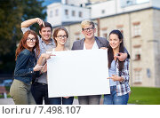 happy teenage students holding white blank board. Стоковое фото, фотограф Syda Productions / Фотобанк Лори