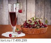Купить «Натуральный вишневый напиток в стакане и свежие вишни в корзине на столе», фото № 7499299, снято 18 июля 2014 г. (c) Александр Волков / Фотобанк Лори