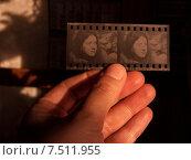 Рука держит кусочек негативной чёрно-белой плёнки. Редакционное фото, фотограф Елена Алексеева / Фотобанк Лори
