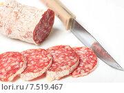 Колбаса салями и нож на белом фоне. Стоковое фото, фотограф Яна Королёва / Фотобанк Лори
