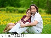 Купить «Счастливая пара средних лет сидит на траве в весеннем парке», фото № 7522711, снято 24 мая 2015 г. (c) Володина Ольга / Фотобанк Лори