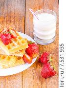 Домашние вафли с клубникой и кленовым сиропом и стакан молока на столе. Стоковое фото, фотограф Sanda Stanca / Фотобанк Лори