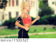 sporty woman running with smartphone and earphones. Стоковое фото, фотограф Syda Productions / Фотобанк Лори