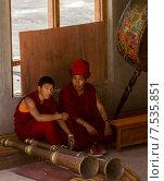 Два монаха музыканта с тибетскими священными трубами (Дунгчен) и барабанами отдыхают во время перерыва на фестивале танца Цам (Chaam) в монастыре Курча (Karsha) в Занскаре (Гималаи, северная Индия) (2012 год). Редакционное фото, фотограф Олег Иванов / Фотобанк Лори