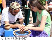 Купить «Гончар дает урок мастер-класса девушке по изготовлению глиняных изделий», фото № 7549647, снято 12 июня 2015 г. (c) Виталий Матонин / Фотобанк Лори