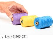 Купить «Катушки с разноцветными нитками и рука на белом фоне», эксклюзивное фото № 7563051, снято 14 июня 2015 г. (c) Яна Королёва / Фотобанк Лори