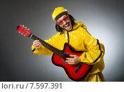 Купить «Funny man wearing yellow suit and playing guitar», фото № 7597391, снято 22 апреля 2015 г. (c) Elnur / Фотобанк Лори