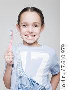 Маленькая девочка чистит зубы зубной щеткой на сером фоне. Стоковое фото, фотограф Дмитрий Булин / Фотобанк Лори