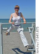 Купить «Молодая женщина занимается на уличном тренажере. Здоровый образ жизни», фото № 7641875, снято 2 июля 2015 г. (c) Ирина Борсученко / Фотобанк Лори