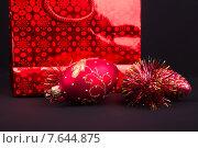 Красный и золотой подарочный пакет на темном фоне. Стоковое фото, фотограф Владимир Ходатаев / Фотобанк Лори
