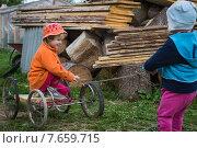 Купить «Дети катаются на сломанной коляске в деревне», фото № 7659715, снято 18 июня 2015 г. (c) Юлия Юриева / Фотобанк Лори