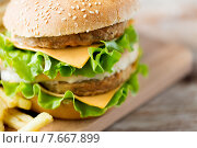 Купить «close up of hamburger or cheeseburger on table», фото № 7667899, снято 21 мая 2015 г. (c) Syda Productions / Фотобанк Лори