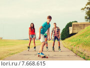 Купить «group of smiling teenagers with roller-skates», фото № 7668615, снято 10 августа 2014 г. (c) Syda Productions / Фотобанк Лори