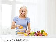 Купить «smiling woman squeezing fruit juice at home», фото № 7668843, снято 26 апреля 2015 г. (c) Syda Productions / Фотобанк Лори