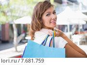 Купить «Portrait of smiling woman holding shopping bag and looking over the shoulder at camera», фото № 7681759, снято 3 марта 2015 г. (c) Wavebreak Media / Фотобанк Лори