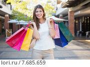 Купить «Portrait of smiling woman with shopping bags looking at camera», фото № 7685659, снято 3 марта 2015 г. (c) Wavebreak Media / Фотобанк Лори