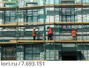 Купить «Рабочие-строители ремонтируют фасад здания за сеткой», фото № 7693151, снято 16 июля 2015 г. (c) Жанна Коноплева / Фотобанк Лори