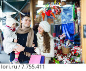 Купить «Happy family choosing Christmas decoration at Christmas market», фото № 7755411, снято 20 июня 2019 г. (c) Яков Филимонов / Фотобанк Лори