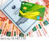 Купить «Сберегательная книжка и пластиковая карта Сбербанка лежат на пятитысячных купюрах», фото № 8147715, снято 24 июля 2015 г. (c) Владимир Сергеев / Фотобанк Лори