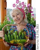 Женщина на балконе с корзинкой огурцов, фото № 8316383, снято 31 августа 2013 г. (c) Элина Гаревская / Фотобанк Лори