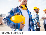 Купить «close up of builder holding hardhat at building», фото № 8380435, снято 21 сентября 2014 г. (c) Syda Productions / Фотобанк Лори