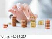 Купить «close up of female hand putting coins into columns», фото № 8399227, снято 2 июля 2015 г. (c) Syda Productions / Фотобанк Лори