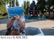 """Купить «Женщина держит плакат с надписью """"Жилье у моря"""" около паровоза ЭЛЛ-2500, который стоит в районе Севастопольского железнодорожного и автобусного вокзалов, Республика Крым», фото № 8408983, снято 21 июля 2015 г. (c) Николай Винокуров / Фотобанк Лори"""