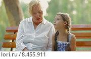 Купить «Женщина читает книжку девочке в парке», видеоролик № 8455911, снято 20 июня 2015 г. (c) Tatiana Kravchenko / Фотобанк Лори