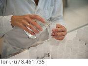 Лаборант разливает реактив по банкам. Женские руки крупным планом. Стоковое фото, фотограф Александра Прохорова / Фотобанк Лори