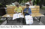 Купить «Дети сидят на лавочке и наклеивают в книгу наклейки», эксклюзивный видеоролик № 8476787, снято 22 июля 2015 г. (c) Алексей Бок / Фотобанк Лори