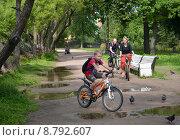Купить «Семья на велосипедах едет по дорожке парка. Фокус на женщине», фото № 8792607, снято 24 июля 2015 г. (c) Ирина Борсученко / Фотобанк Лори