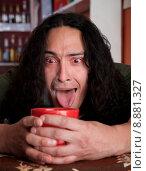 Купить «Tired Latino man cradling red coffee cup», фото № 8881327, снято 24 мая 2018 г. (c) PantherMedia / Фотобанк Лори