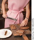 Девушка в розовом платье режет на кухне ножом чёрный хлеб. Стоковое фото, фотограф Олег Абрамов / Фотобанк Лори