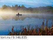 Одинокий рыбак в лодке на озере на рассвете. Стоковое фото, фотограф Денис Приходько-Муханов / Фотобанк Лори