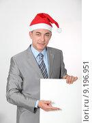 Купить «Smiling businessman with Santa hat showing white board», фото № 9196951, снято 29 февраля 2020 г. (c) PantherMedia / Фотобанк Лори