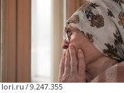 Одинокая старуха в платке и очках смотрит в окно. Стоковое фото, фотограф Дарья Филимонова / Фотобанк Лори