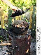 Открытый чугунок с мясом. В руке крышка от чугунка (2013 год). Стоковое фото, фотограф Манапова Екатерина / Фотобанк Лори